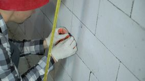 L'inclinaison a tiré du travailleur de la construction installant des brides sur le mur de bloc banque de vidéos