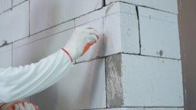 L'inclinaison a tiré du travailleur insérant des doigts dans des trous forés dans le mur de bloc banque de vidéos
