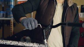 L'inclinazione-giù ha sparato del riparatore professionista del giovane in cuffie che riparano il manubrio della bici facendo uso archivi video