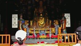 L'inclinazione ha sparato sulla statua buddista pregante della gente in tempio cinese stock footage