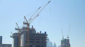 L'inclinazione su panorama delle gru di costruzione enormi è in costruzione non finita nella grande città moderna video d archivio