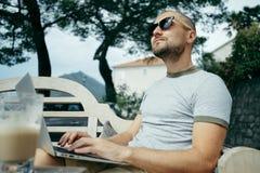 L'indépendant dans des lunettes de soleil travaille sur un ordinateur portable dans un café d'été à côté de t Photo libre de droits