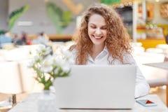 L'indépendant féminin attirant travaille à distance sur l'ordinateur portable portatif, heureux d'être favorisé, entouré avec les photographie stock libre de droits