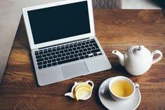 L'indépendant utilise l'ordinateur portable pour le travail à distance tout en dînant petit déjeuner au restaurant moderne images stock