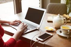 L'indépendante de femme utilise l'ordinateur portable pour le travail à distance tout en dînant petit déjeuner au restaurant mode Images libres de droits