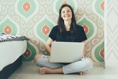 L'indépendante de fille avec l'ordinateur portable s'assied sur le plancher et les rires image libre de droits