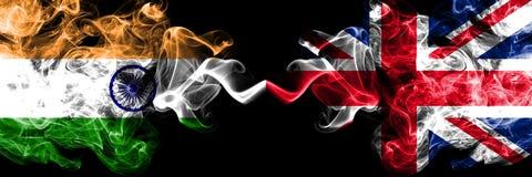 L'Inde contre le Royaume-Uni, drapeaux britanniques de fumée placés côte à côte Drapeaux soyeux colorés épais de fumée d' photos stock
