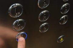 L'index de la main masculine dans l'ascenseur appuie sur le bouton du premier étage, qui rougeoie bleu Plan rapproché Surface mét Photos stock