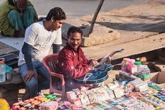 L'indiano con l'amico sull'argine di Gange gioca un Gu semi-acustico Immagine Stock