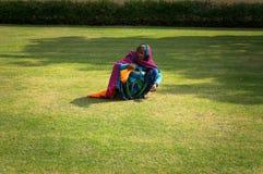 L'indiano femminile falcia il prato inglese della mano con erba verde Duro lavoro della gente povera in India Fotografia Stock