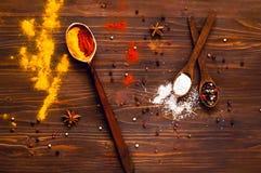 L'indiano tradizionale fiorisce Holi, le spezie, i cucchiai di legno e gli ingredienti su un fondo scuro Fondo con le spezie Vist Fotografie Stock