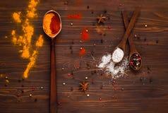 L'indiano tradizionale Holi colora la polvere, le spezie, i cucchiai del metallo e gli ingredienti su un fondo di legno Fondo con Immagini Stock Libere da Diritti