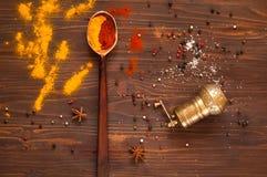 L'indiano tradizionale Holi colora la polvere, le spezie, i cucchiai del metallo e gli ingredienti su un fondo di legno Fondo con Fotografia Stock Libera da Diritti
