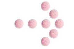 L'indicateur de flèche des sucreries et de la gelée roses et blanches sur b blanc Images libres de droits