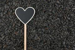 L'indicateur sous forme de coeur se trouve sur des graines de tournesol Photos stock