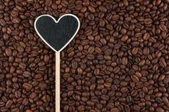 L'indicateur sous forme de coeur se trouve sur des grains de café Image libre de droits