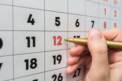 L'indicatore della mano indica il dodicesimo numero nel calendario murale immagini stock