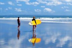 L'Indonesia, isola di Bali, Kuta - 10 ottobre 2017: Surfisti con un surf che camminano lungo la spiaggia Scuola di praticare il s Immagini Stock