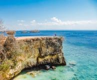 L'Indonesia - la ragazza e la scogliera rosa della spiaggia fotografia stock