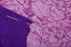 L'indumento tricottato è porpora con i ferri da maglia attaccati ed i grovigli del filo, di cui è tricottato immagine stock