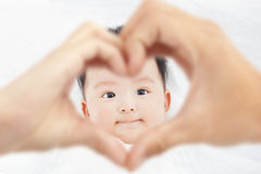 L'infante sveglio e sorridente con i genitori ama le mani Immagini Stock