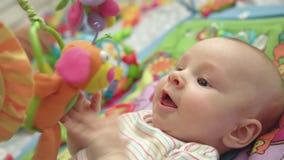L'infante sveglio si diverte con i giocattoli Chiuda su del bambino felice che si trova sulla stuoia di sviluppo stock footage