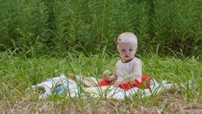L'infanzia di HD, ragazza del bambino sta giocando la seduta sulla terra con i suoi giocattoli nel parco archivi video
