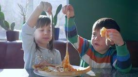 L'infanzia felice, amici allegri mangia gli alimenti industriali durante il pranzo in pizzeria vicino alla finestra stock footage