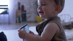 L'infanzia moderna, bambino sta giocando con il telefono cellulare a casa su fondo unfocused