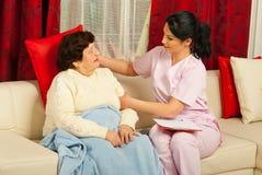 L'infermiera ha messo un cuscino alla donna maggiore immagini stock