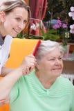 L'infermiera pettina i capelli di un anziano Fotografia Stock Libera da Diritti