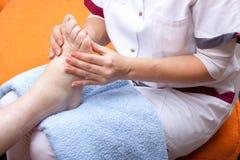 L'infermiera tratta un piede paziente Immagine Stock