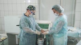 L'infermiere aiuta il chirurgo indossato un abito sterile ed i guanti Medici stanno preparando per chirurgia nel chirurgico archivi video