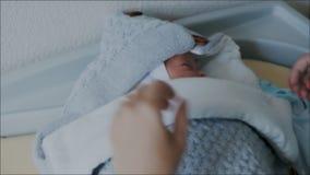 L'infermiere avvolge con attenzione il neonato in una coperta Chiuda sul colpo video d archivio