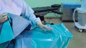 L'infermiere che mette una copertura sterile sulla tavola archivi video