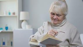 L'infermiere complementare che dà a donna anziana gli occhiali pazienti, ha invecchiato il libro di lettura di signora stock footage