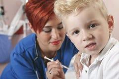 L'infermiere del bambino piccolo gli dà un colpo Immagini Stock