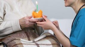 L'infermiere felice che si congratula ha invecchiato signora sul compleanno e muffin dare con la candela video d archivio
