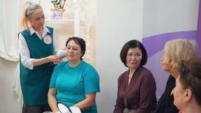 L'infermiere grigio-dai capelli anziano dimostra il massaggio facciale dell'hardware sul cliente al gruppo di donne anziane video d archivio