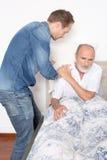 L'infermiere maschio prende la cura dell'uomo più anziano a letto fotografia stock