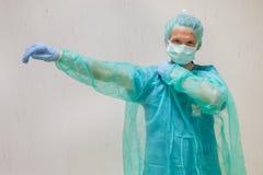 L'infermiere mette sopra un cappotto eliminabile in ospedale Fotografie Stock