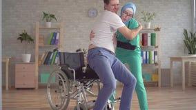L'infermiere musulmano nel hijab aiuta il disabile a alzarsi dalla sedia a rotelle stock footage