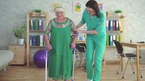 L'infermiere nella clinica di riabilitazione sostiene la donna anziana sulle grucce stock footage