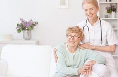 L'infermiere sorridente si siede con la donna più anziana immagine stock