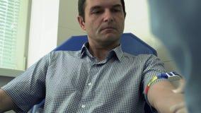 L'infermiere sta effettuando l'analisi del sangue per l'uomo in clinica archivi video