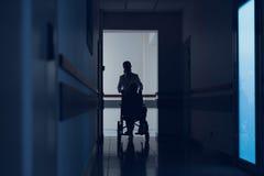 L'infermiere sta spingendo la sedia a rotelle con il paziente nell'ospedale immagine stock