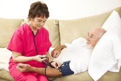 L'infirmière à la maison prend la tension artérielle Photographie stock