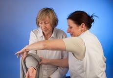 L'infirmière aide une femme agée avec l'habillage Images stock