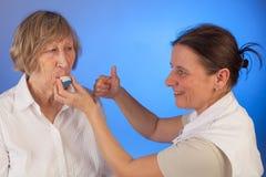 L'infirmière aide une femme supérieure avec son médicament Images stock