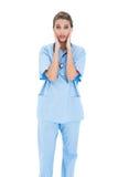 L'infirmière d'une chevelure brune étonnée dans le bleu frotte la pose avec la tête dans des mains Photos libres de droits